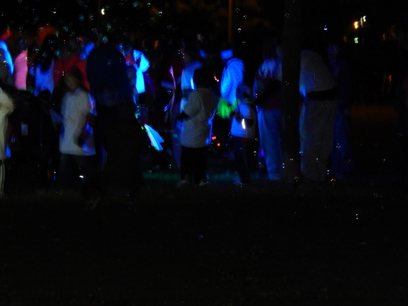 Blowing bubbles at Blacklight Bubble Party 5K